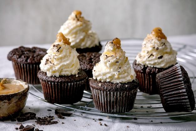 Zelfgemaakte chocolade cupcakes muffins met witte slagroom boter room en gezouten karamel, geserveerd met gehakte donkere chocolade op koelrek op wit tafelkleed.