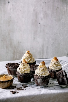 Zelfgemaakte chocolade cupcakes muffins met witte slagroom botercrème en gezouten karamel, geserveerd met gehakte donkere chocolade op koelrek op wit tafelkleed.