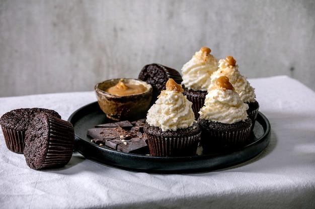 Zelfgemaakte chocolade cupcakes muffins met witte slagroom botercrème en gezouten karamel, geserveerd met gehakte donkere chocolade op zwarte keramische plaat op wit tafelkleed.