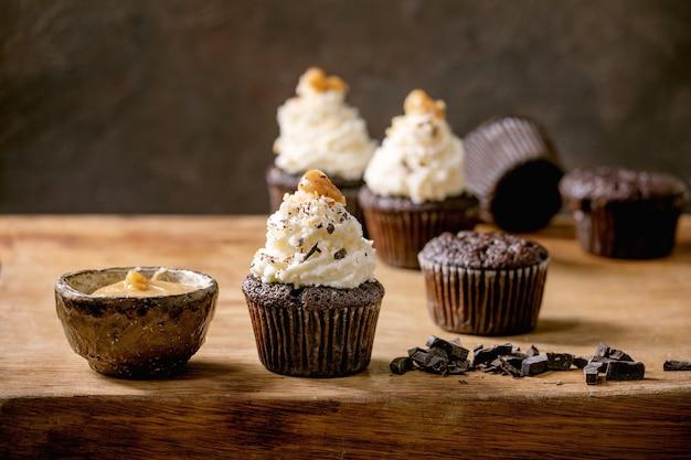 Zelfgemaakte chocolade cupcakes muffins met witte slagroom botercrème en gezouten karamel op keramische plaat, geserveerd met gehakte donkere chocolade op houten tafel.