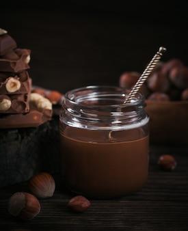 Zelfgemaakte chocolade hazelnootmelk uitgespreid op glazen pot op donkere houten oppervlak
