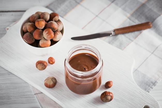 Zelfgemaakte chocolade hazelnootmelk verspreid op een witte houten tafel