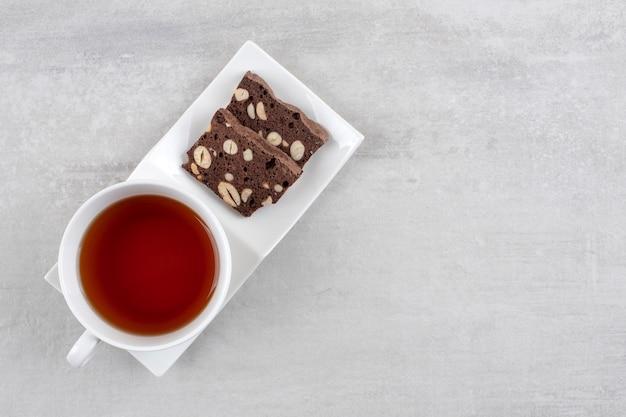 Zelfgemaakte chocoladebrownies en een kopje thee op een schaal, op het marmer.