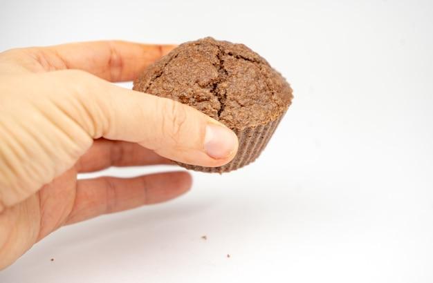 Zelfgemaakte chocoladebruine muffins in een hand. geïsoleerd op een witte achtergrond