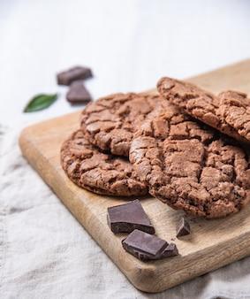 Zelfgemaakte chocoladekoekjes met chocoladeschilfers op houten scherpe raad op een lichte lijst. vooraanzicht en kopieerruimte