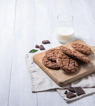 Zelfgemaakte chocoladekoekjes met chocoladeschilfers op snijplank en glas melk op een lichte houten tafel. vooraanzicht en kopieerruimte