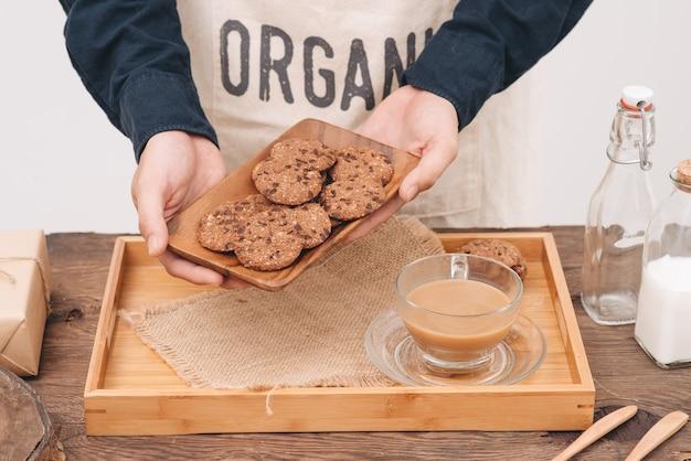 Zelfgemaakte chocoladekoekjes op plaat in mannelijke handen.