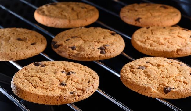 Zelfgemaakte chocoladeschilferkoekjes bakken op rek in huisoven. selectieve focus close-up