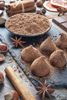 Zelfgemaakte chocoladetruffels bestrooid met cacaopoeder en diverse chocolade met noten en andere kruiden op rustieke oude keukentafel.