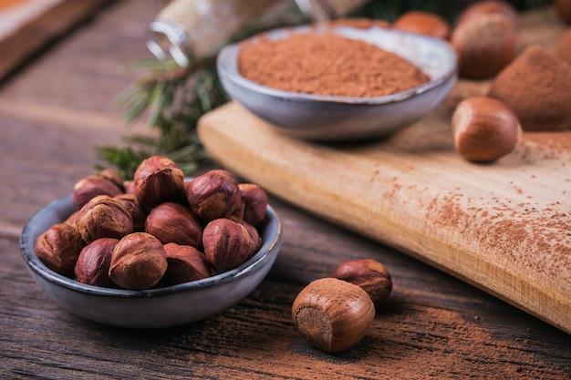Zelfgemaakte chocoladetruffels, hazelnoten, amandelen en cacaopoeder op houten snijplank. winter vakantie decoratie.