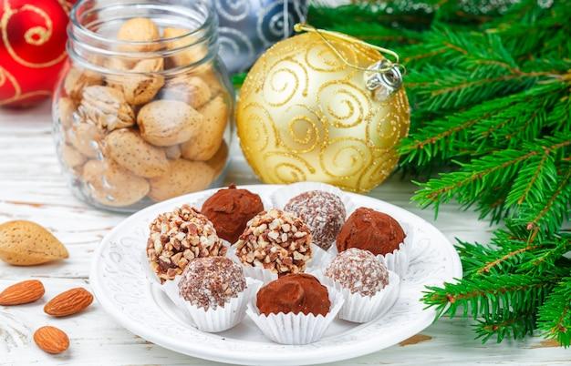 Zelfgemaakte chocoladetruffels met amandelen, kokosnoot en koekjes kruimelen in een witte plaat