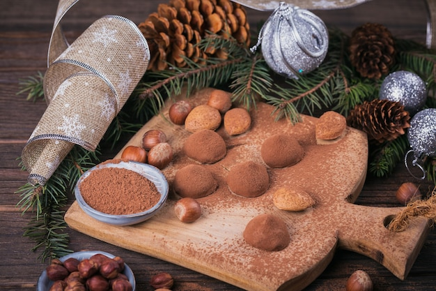 Zelfgemaakte chocoladetruffels, noten, amandelen en cacaopoeder op houten snijplank. winter vakantie decoratie.