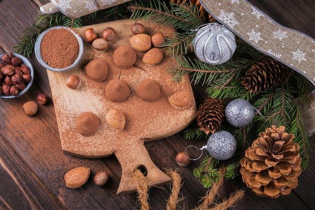 Zelfgemaakte chocoladetruffels, noten, amandelen en cacaopoeder op houten snijplank. winter vakantie decoratie. Premium Foto
