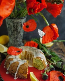 Zelfgemaakte citroen gebonden cake en rode bloemen. vliegende vlinder