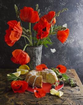 Zelfgemaakte citroen gebonden cake en rode bloemen. vliegende vlinders