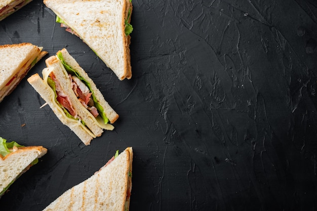 Zelfgemaakte club sandwich met kalkoen, op zwarte achtergrond, bovenaanzicht met kopie ruimte voor tekst