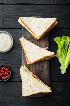 Zelfgemaakte club sandwich met kalkoen, op zwarte houten tafel, bovenaanzicht
