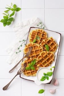 Zelfgemaakte courgettewafels met kaas, saus en bladbasilicum op witte achtergrond. concept van keto-dieetvoeding.