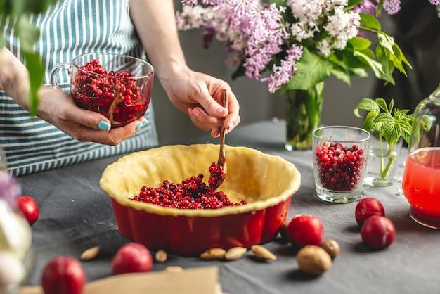 Zelfgemaakte cranberrytaart koken. leg in de ovenschaal met het deeg een lepel verse veenbessen