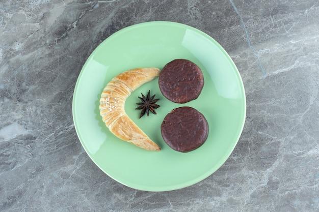 Zelfgemaakte croissant en chocoladekoekjes op groene plaat.