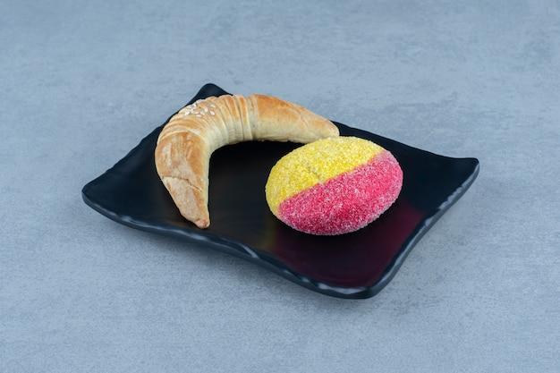 Zelfgemaakte croissant en koekje op perzikvorm op zwarte plaat.
