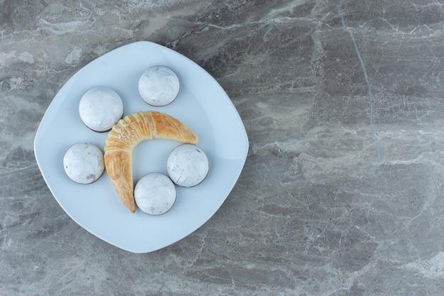 Zelfgemaakte croissant met koekjes op witte plaat.