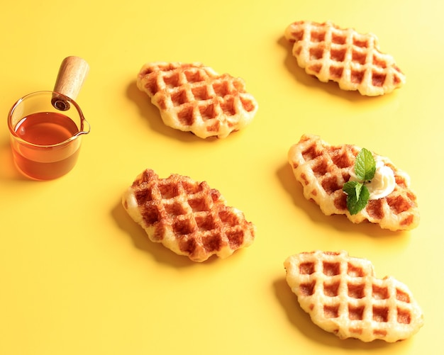 Zelfgemaakte croissant wafel (croffle) tegen gele achtergrond. geserveerd met honing of ahornsiroop