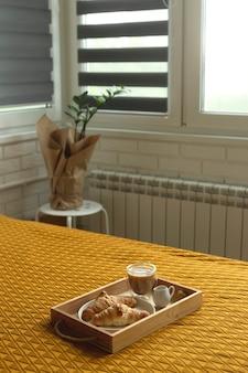 Zelfgemaakte croissants en koffie op een houten dienblad