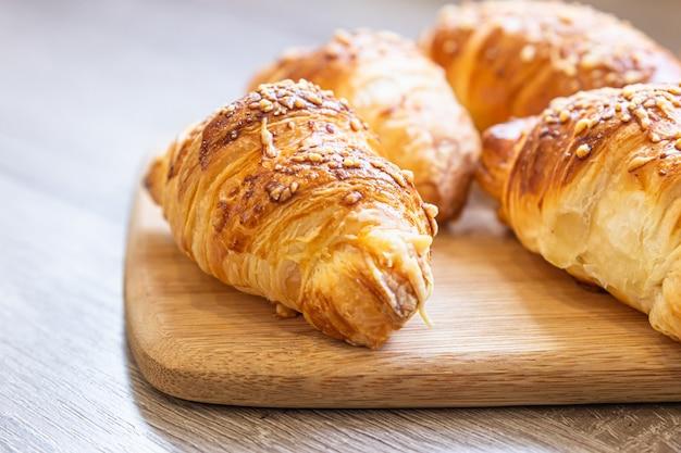 Zelfgemaakte croissants met kaas op een houten bord. bakken als ontbijt.