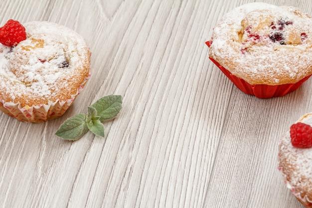Zelfgemaakte cupcakes bestrooid met poedersuiker en verse munt op de houten planken. bovenaanzicht.