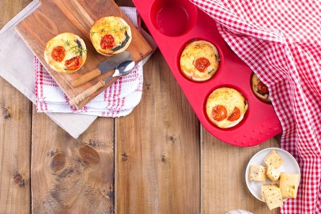 Zelfgemaakte cupcakes met kaas en cherry tomaten op een houten bord