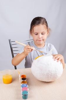 Zelfgemaakte decoratie voor halloween, een kind schildert een pompoen uit papier en servetten, een hobby op zelfisolatie.