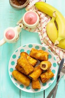 Zelfgemaakte dessert van gebakken bananen gebakken gevuld met chocolade bovenaanzicht plat lag oppervlak