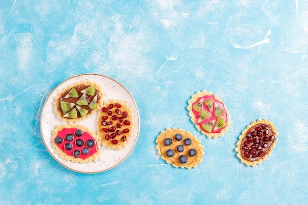 Zelfgemaakte desserts met bosbessen, plakjes kiwi en granaatappelpitjes.