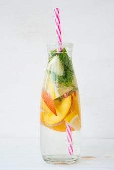 Zelfgemaakte detox drankje van citroen en perzik in een fles.