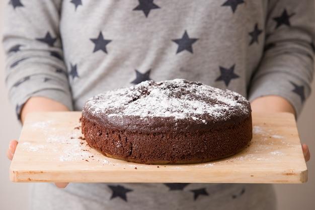 Zelfgemaakte donkere chocolade verjaardagstaart met roomchocoladeschilfers en witte suikerpoeder op de top