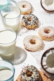 Zelfgemaakte donuts met kokos en zwarte sesamzaadjes in veelkleurig glazuur en glazen met melk
