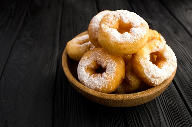 Zelfgemaakte donuts met poedersuiker in bruine kom