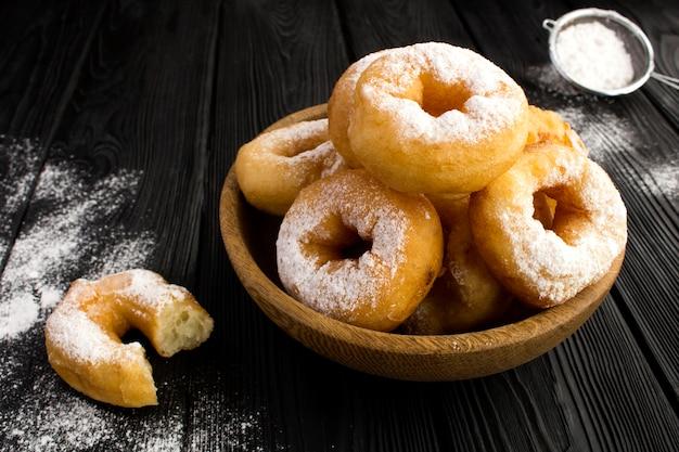 Zelfgemaakte donuts met poedersuiker in de bruine kom