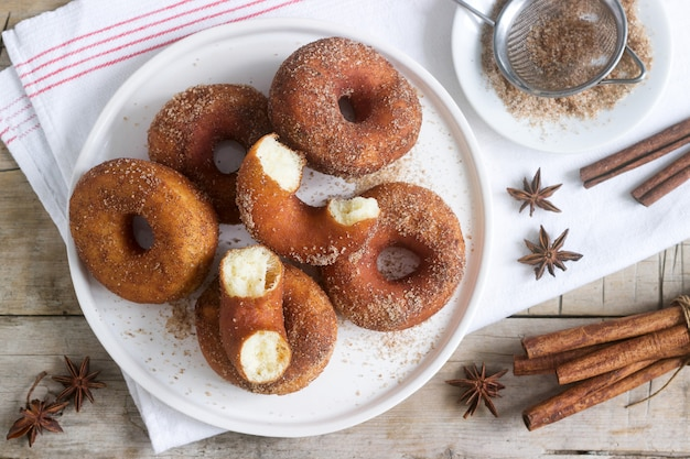 Zelfgemaakte donuts met suiker en kaneel op een houten achtergrond. rustieke stijl.
