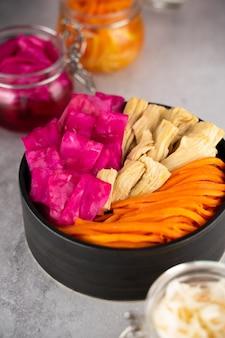 Zelfgemaakte dorp gefermenteerde zuurkool, rode kool en koreaanse wortel, asperges. veganistische salade in zwarte keramische kom. probiotica darm gezondheid voedsel concept. supplement en adaptogenen. superfood, bovenaanzicht
