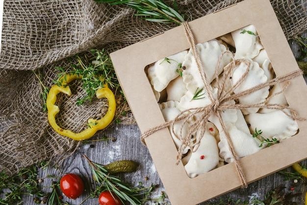 Zelfgemaakte dumplings in een ambachtelijke doos op een houten tafel. russische en oekraïense keuken.