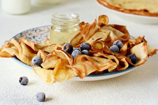 Zelfgemaakte dunne pannenkoeken met bessen, honing en melk voor het ontbijt op een lichte achtergrond.
