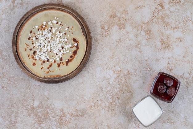 Zelfgemaakte dunne verse pannenkoeken met aardbeienjam