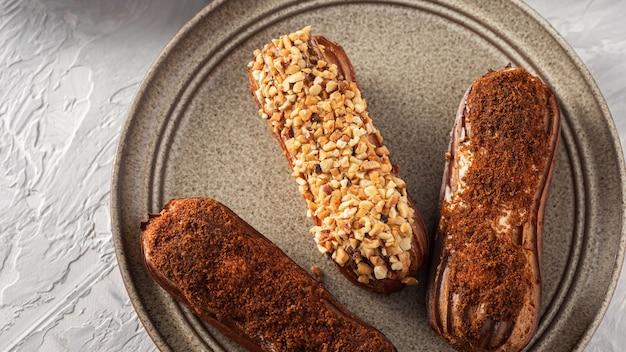 Zelfgemaakte eclairs versierd met noten en cacao op de plaat, geglazuurde patisserie