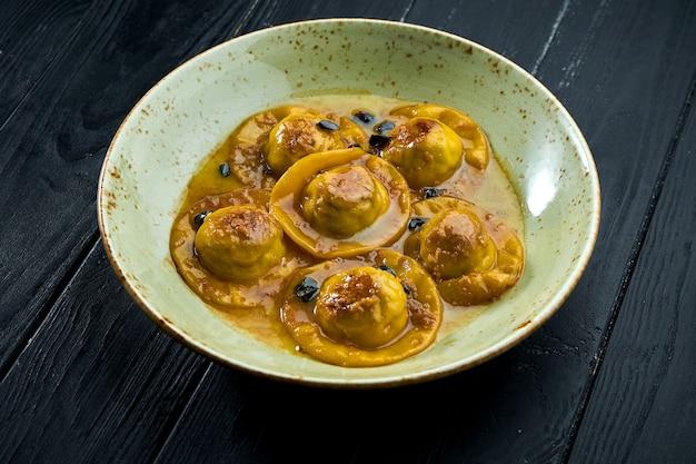 Zelfgemaakte en verrukkelijke ravioli met eendenborst en veenbessen, geserveerd met saus in een blauw bord op een donkere houten achtergrond.