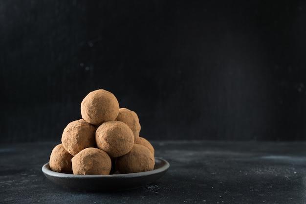 Zelfgemaakte energieballen met cacao, kokosnoot op zwart. gezond eten voor kinderen en veganisten, snoepvervanger.