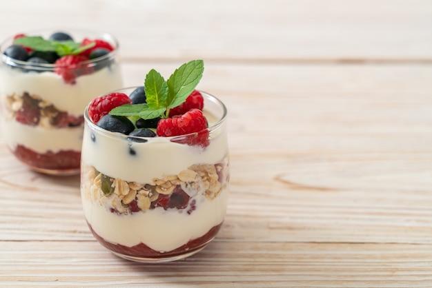 Zelfgemaakte frambozen en bosbessen met yoghurt en granola - gezonde voedingsstijl