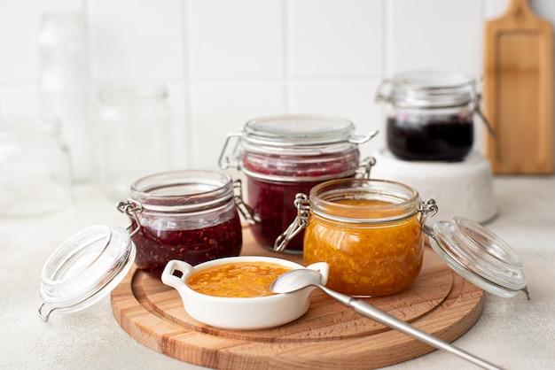 Zelfgemaakte frambozen-, mandarijn- en bramenjam in glazen potten