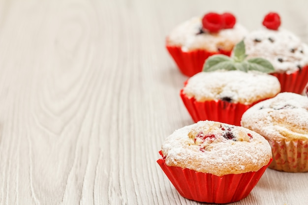 Zelfgemaakte fruitmuffins bestrooid met poedersuiker en verse frambozen op houten bureau. kerst snoep en gebak.